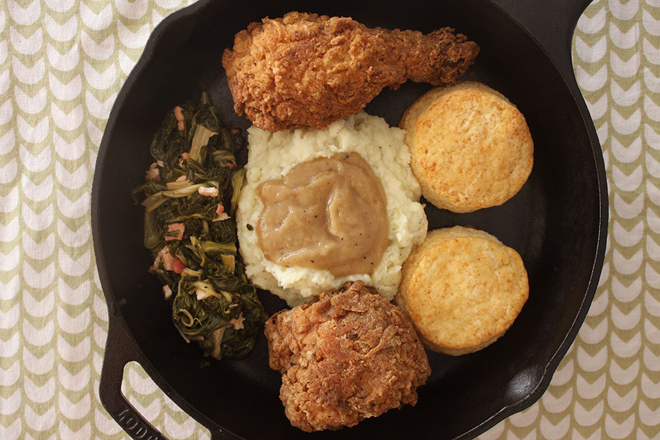 A Southern dinner of greens, fried chicken, biscuits, roasted chicken gravy and mashed potatoes